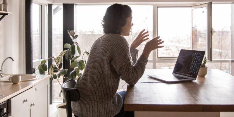 Frau mit Laptop in Küche.